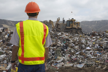 landfill site: Worker watching digger moving waste at landfill site