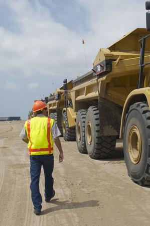 landfill site: Lavoratore a piedi vicino al camion discarica