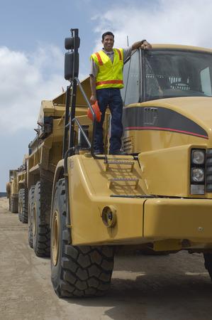 landfill site: Lavoratore in piedi sul camion in discarica, ritratto LANG_EVOIMAGES