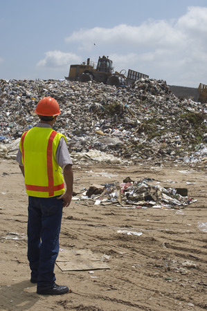 Worker watching digger moving waste at landfill site Stock Photo - 3811560