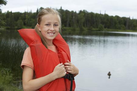 one teenage girl only: USA, Alaska, teenage girl wearing life jacket by lake, portrait