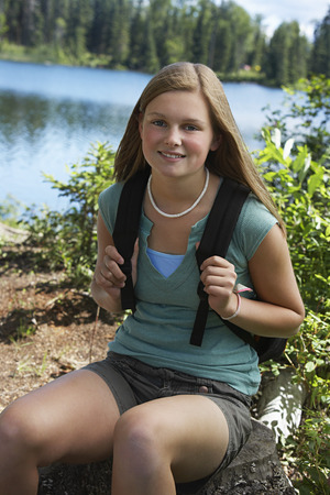 long lake: USA, Alaska, teenage girl wearing backpack at lake, portrait