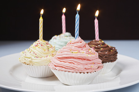 Colourful cupcakes with birthday candles on plate Stock Photo - 3811344