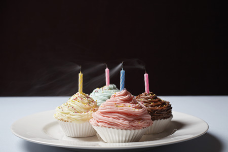 blowed: Colourful cupcakes with blowed birthday candles on plate