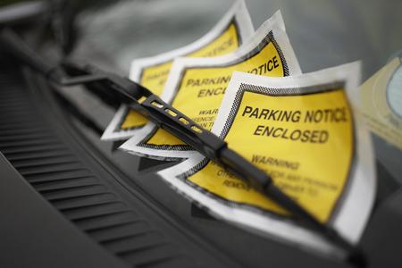 Parking tickets under windshield wiper, close-up Stock Photo