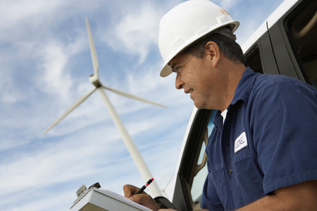 writing activity: Engineer writing on clipboard by car at wind farm