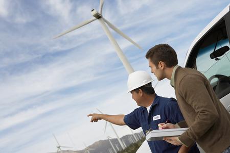 Engineers examining wind turbines by car at wind farm