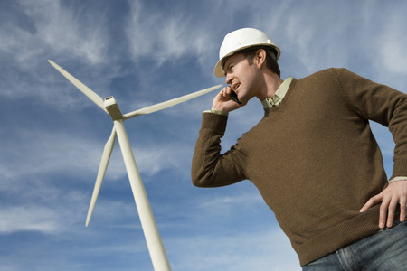 Engineer using mobile phone at wind farm Stock Photo - 3811483