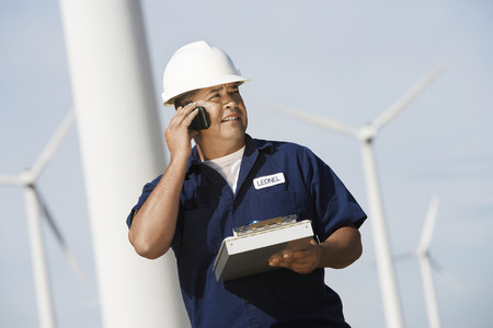 Engineer using mobile phone at wind farm Stock Photo - 3811336