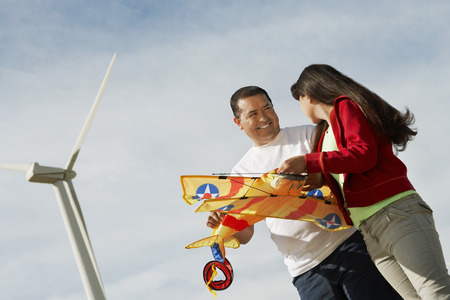 Girl (7-9) holding airplane kite with father at wind farm Stock Photo - 3811353