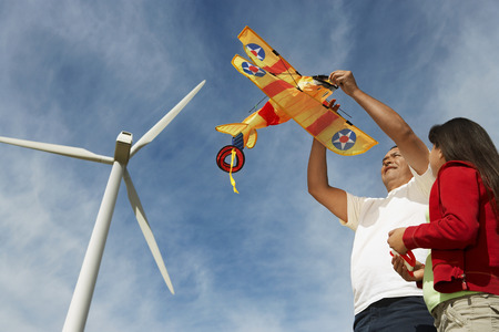 Father holding airplane kite with daughter (7-9) at wind farm Stock Photo - 3811470
