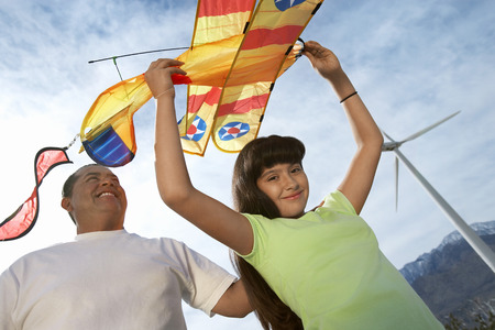 Girl (7-9) holding airplane kite with father at wind farm Stock Photo - 3811434