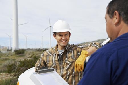 Ingenieros cerca de los aerogeneradores en parque eólico