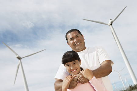 Father embracing daughter (7-9) at wind farm, portrait Stock Photo - 3811306