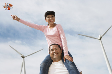 Girl (7-9) sitting on fathers shoulders at wind farm, portrait Stock Photo - 3811338