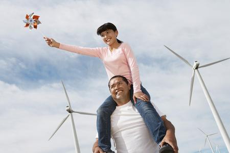 Girl (7-9) assis sur les épaules des pères au parc éolien Banque d'images - 3811327