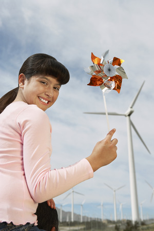 Girl (7-9) holding windmill, sitting on fathers shoulders at wind farm, portrait Stock Photo - 3811334