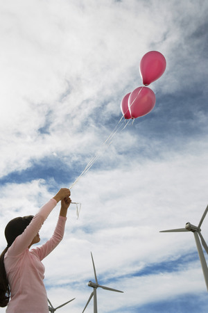 Girl (7-9) playing with balloons at wind farm Stock Photo - 3811310