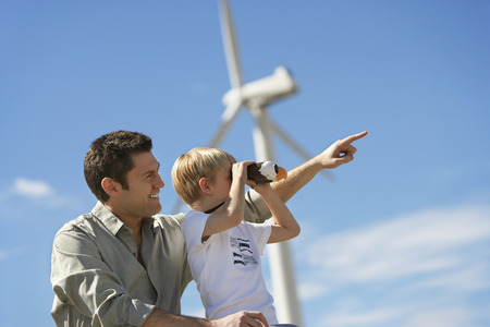 Boy (7-9) using binoculars with father at wind farm Stock Photo - 3811437
