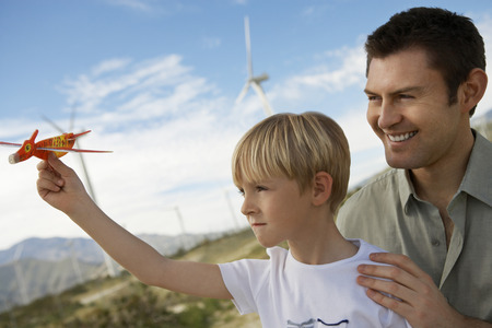 parent and child: Boy (7-9) holding toy glider with father at wind farm LANG_EVOIMAGES