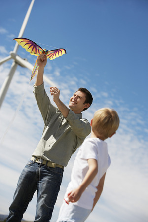 Father and son (7-9) playing with kite at wind farm Stock Photo - 3812165