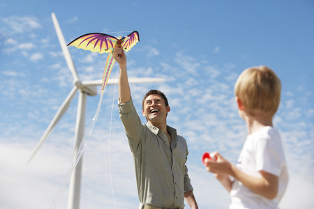 Father and son (7-9) playing with kite at wind farm Stock Photo - 3811607