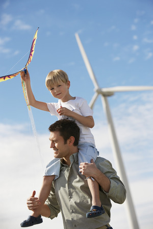 Boy (7-9) holding kite, sitting on fathers shoulders at wind farm Stock Photo - 3811610