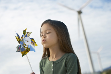 head toy: Girl (5-6) blowing toy windmill at wind farm LANG_EVOIMAGES