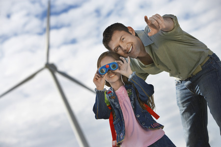 Girl (5-6) using binoculars with father at wind farm Stock Photo - 3811648