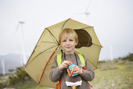 Boy (7-9) with umbrella at wind farm, portrait Stock Photo - 3811601