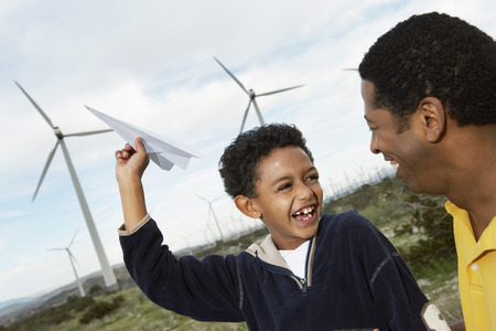 Father and son (7-9) playing with paper plane at wind farm Stock Photo - 3811647