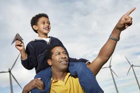 one parent: Boy (7-9) holding paper plane, on fathers shoulders at wind farm