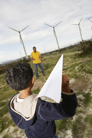 Father and son (7-9) playing with paper plane at wind farm Stock Photo - 3811708