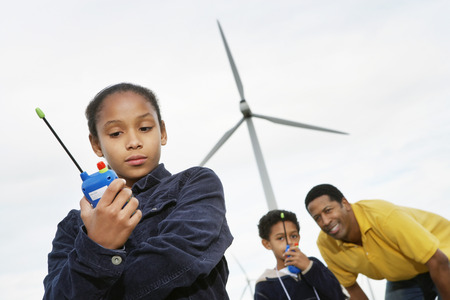Father and children (7-9) playing with walky-talkies at wind farm Stock Photo - 3811589