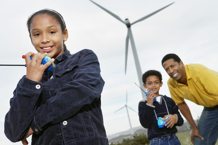 Father and children (7-9) playing with walky-talkies at wind farm Stock Photo - 3811653