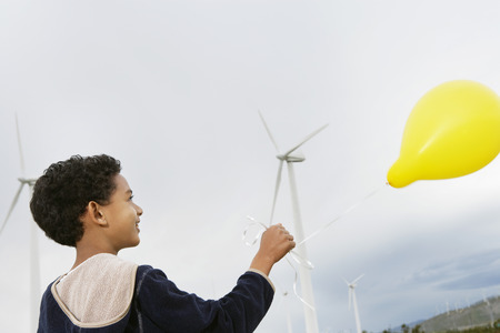 Boy (7-9) playing with balloon at wind farm Stock Photo - 3811588