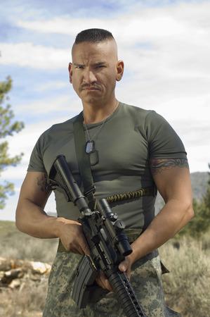holding gun to head: Portrait of soldier with machine gun