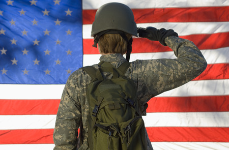 saluting: Soldier saluting in front of American flag