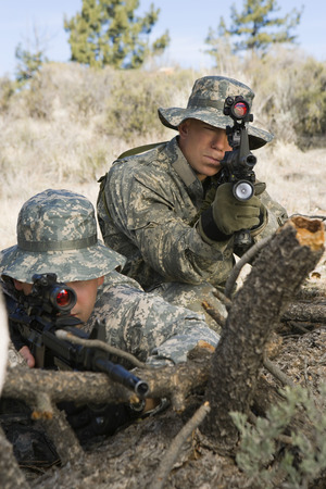 Soldiers aiming machine gun, leaning on log Stock Photo - 3811728