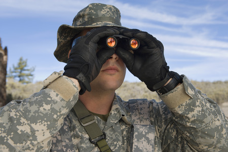 Soldier looking through binoculars, close-up