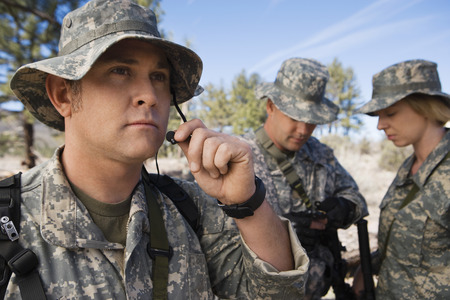 Soldiers in field, focus on one in foreground Stock Photo - 3811726