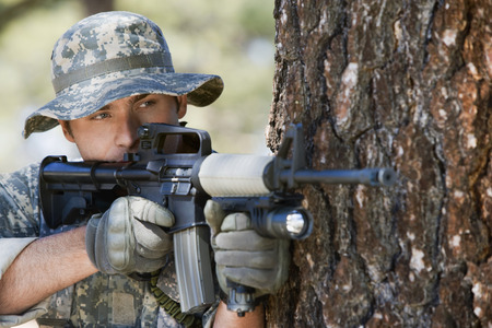 Soldier aiming machine gun, close-up Stock Photo - 3811711