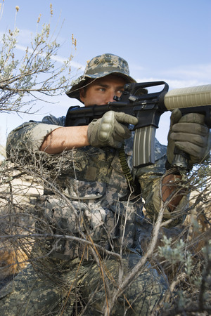 Soldier aiming machine gun, close-up Stock Photo - 3811776