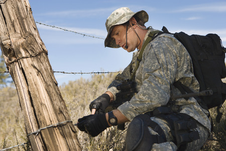 Soldier cutting barbed wire fence Stock Photo - 3811788