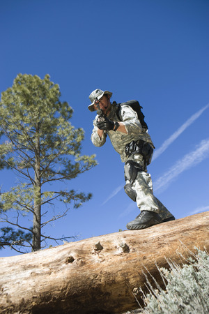 Soldier pointing rifle from tree trunk Stock Photo - 3811768