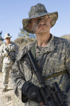 Soldiers in field, focus on soldier in foreground Stock Photo - 3811701