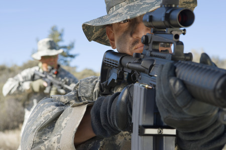 Soldiers aiming rifles in field, focus on soldier in foreground Stock Photo - 3811637