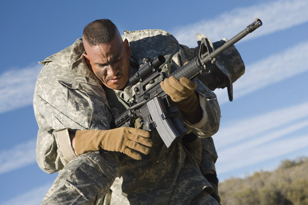 US Army soldier carrying wounded soldier Stock Photo