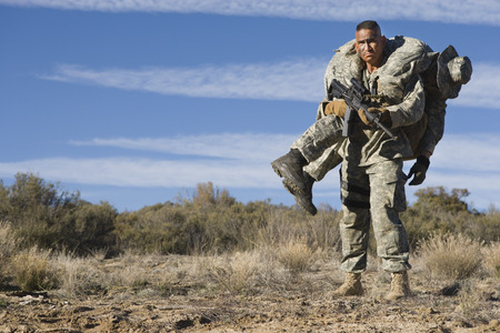 man carrying: US Army soldier carrying wounded friend