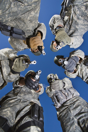 Low angle portrait of soldiers standing in circle, aiming Stock Photo - 3811800